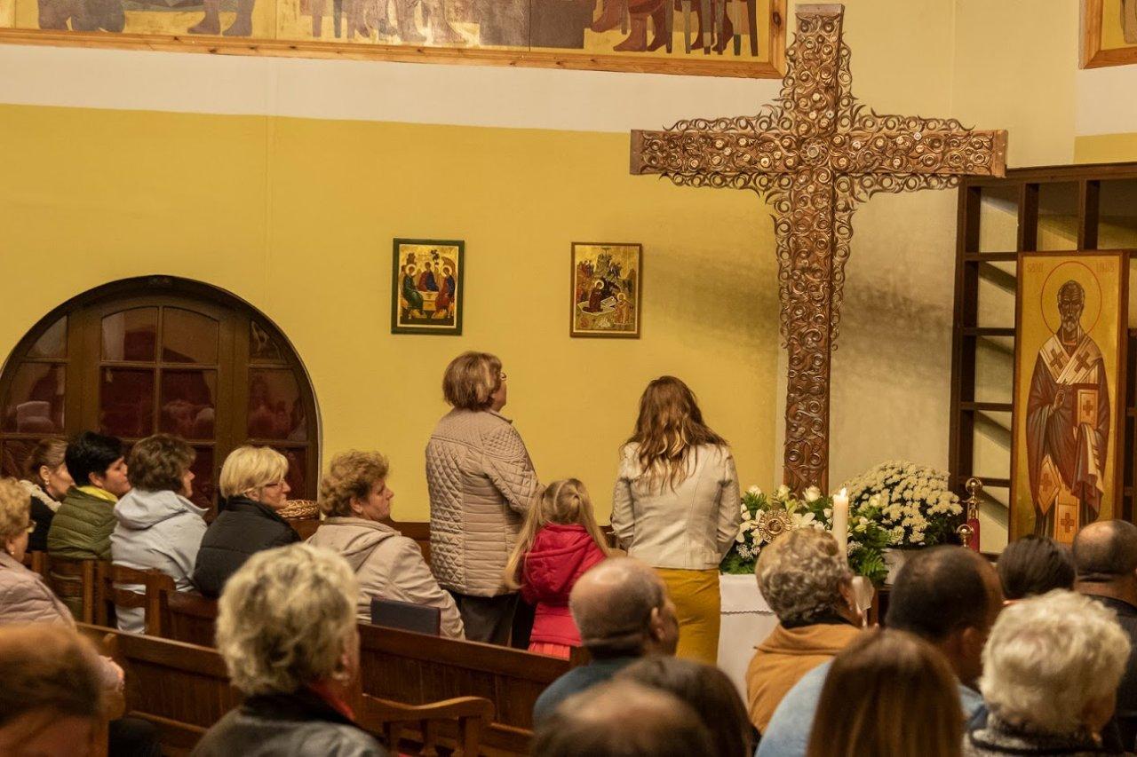 anya gyerekkel az ülében a kereszt előtt